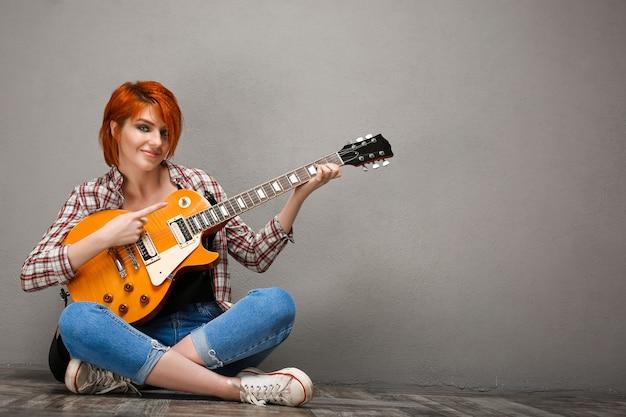 Portret van een jong meisje met gitaar over grijze achtergrond.