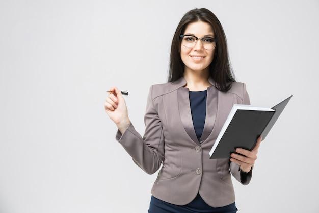 Portret van een jong meisje met glazen met een agenda in haar geïsoleerde handen