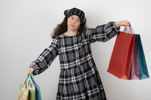 Portret van een jong meisje met het syndroom van down met een heleboel boodschappentas.