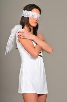 Portret van een jong meisje met in witte jurk met engelenvleugels, handen gevouwen, blinddoek. geïsoleerd op grijze muur Premium Foto