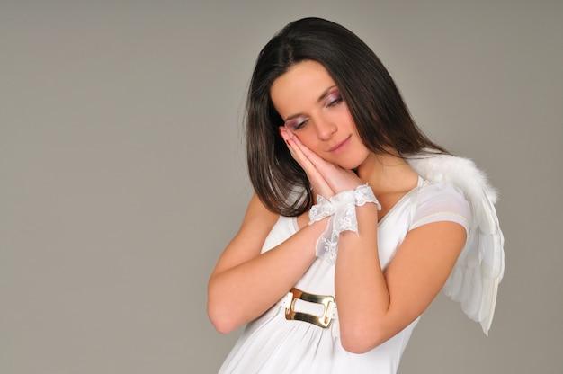 Portret van een jong meisje met in witte jurk met engelenvleugels, handen gevouwen in de buurt van het gezicht