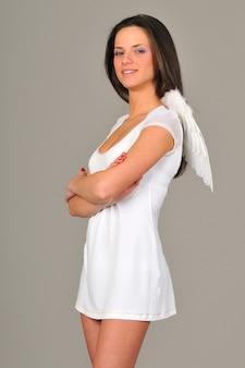Portret van een jong meisje met in witte jurk met engelenvleugels.