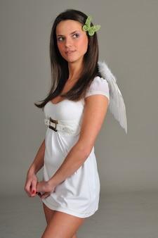 Portret van een jong meisje met in witte jurk met engelenvleugels