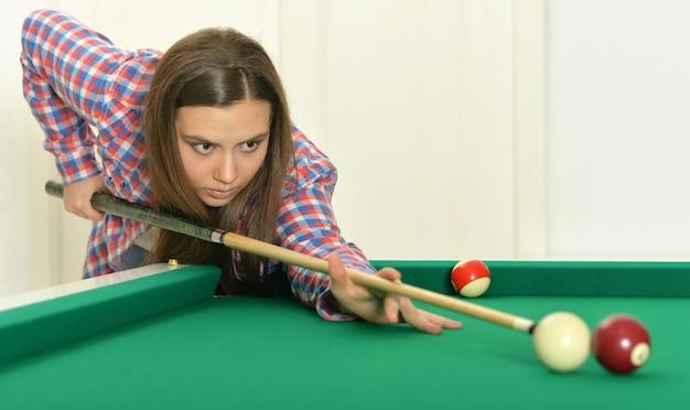 Portret van een jong meisje met keu die biljart speelt