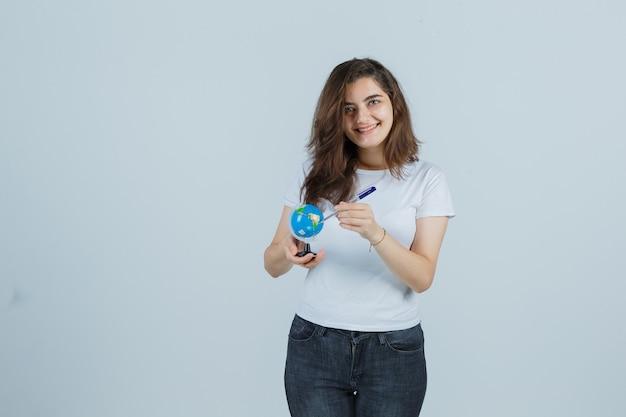 Portret van een jong meisje met pen op wereldbol in t-shirt, spijkerbroek en op zoek gelukkig vooraanzicht