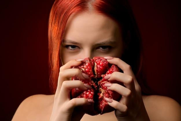 Portret van een jong meisje met rood haar en granaatappelfruit dat haar gezicht bedekt op een rode achtergrond