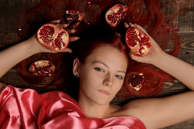 Portret van een jong meisje met rood haar en granaatappelfruit in haar haar op een bruine achtergrond