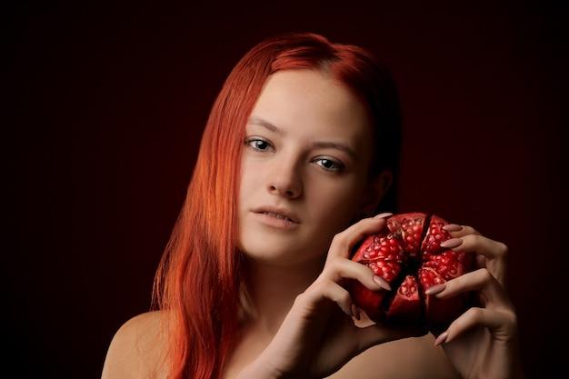 Portret van een jong meisje met rood haar en granaatappelfruit in handen op rode achtergrond