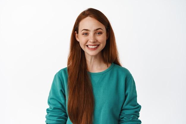 Portret van een jong meisje met rood lang haar, glimlachend witte tanden, vastberaden en gelukkig, staande in groene blouse op wit.