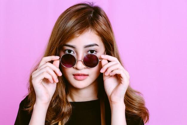 Portret van een jong meisje met zonnebril op roze achtergrond