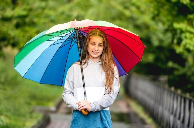 Portret van een jong meisje onder kleurrijke paraplu in regenachtig park