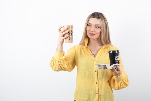 Portret van een jong meisje op zoek naar kopjes koffie op wit.