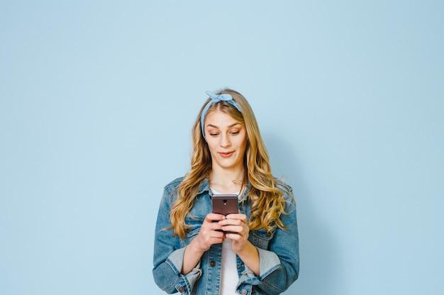 Portret van een jong meisje verbaasd waarom ze in haar mobiele telefoon geïsoleerd op een blauwe achtergrond ziet
