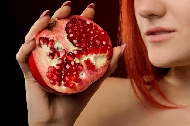 Portret van een jong meisjesclose-up met rood haar en granaatappelfruit op een rode achtergrond
