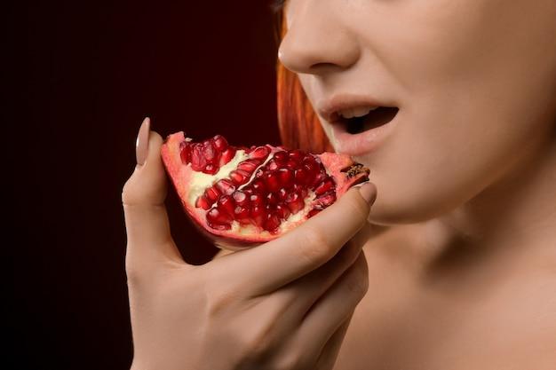 Portret van een jong meisjesclose-up met rood haar en het eten van granaatappelfruit op een rode achtergrond