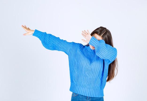 Portret van een jong meisjesmodel dat de schar op witgrijs laat bewegen.