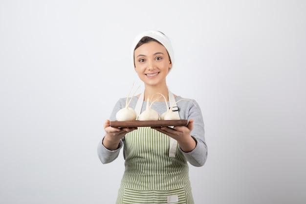 Portret van een jong meisjesmodel dat een houten plank met witte radijs houdt.
