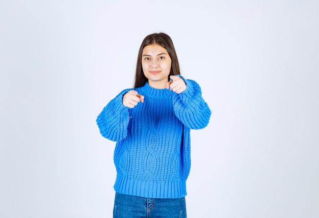 Portret van een jong meisjesmodel dat staat en naar voren wijst