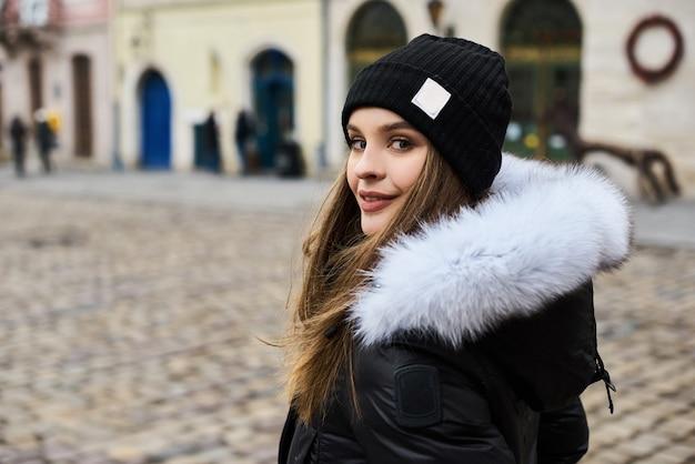 Portret van een jong modieus meisje die op de straat van de stad in de wintertijd lopen