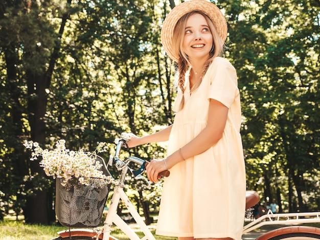 Portret van een jong mooi glimlachend hipstermeisje in trendy zomerjurk