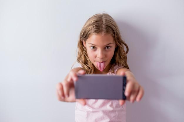 Portret van een jong mooi jong geitje gebruikend een mobiele telefoon en nemend een selfie met haar uit tong. witte muur. kinderen binnenshuis. lifestyle
