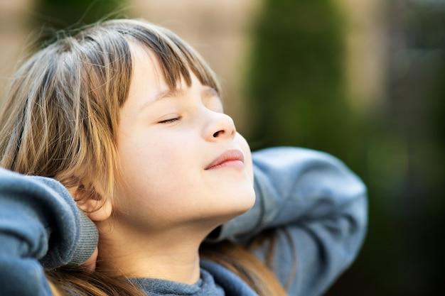 Portret van een jong mooi kindmeisje met lang haar genieten van warme zonnige dag in de zomer buiten