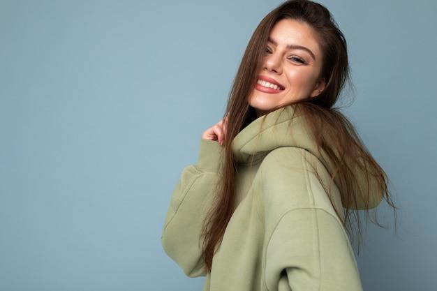 Portret van een jong mooi lachend meisje in een stijlvolle hipster groene hoodie