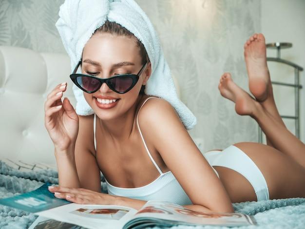 Portret van een jong mooi lachend meisje in witte lingerie en een handdoek op het hoofd