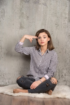 Portret van een jong mooi meisje in een geruit hemd dat naar het hoofd wijst