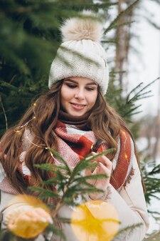 Portret van een jong mooi meisje in een hoed tussen winterkerstbomen met verlichting. een park met kerstbomen op de achtergrond. kerststemming. verven.