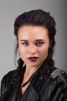 Portret van een jong mooi meisje in een lederen jas met grijze ogen en make-up.
