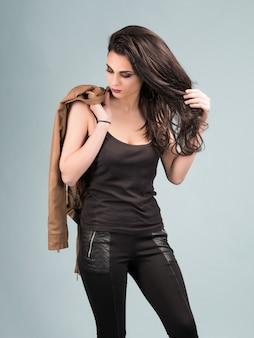 Portret van een jong mooi meisje in een lederen jas met lang bruin haar
