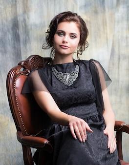 Portret van een jong mooi meisje in een zwarte jurk met bruin haar en grijze ogen.
