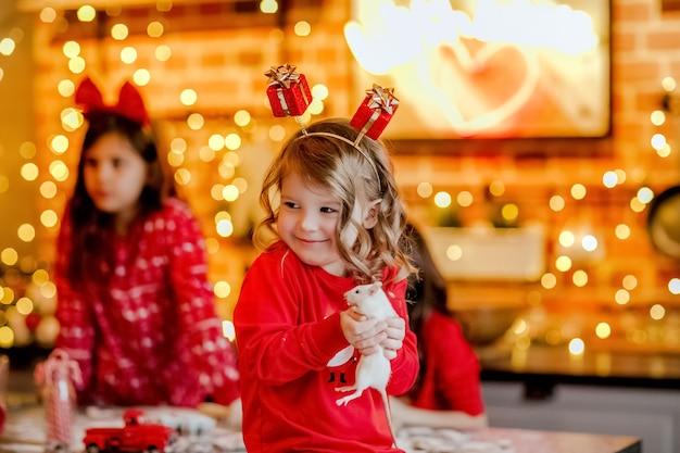 Portret van een jong mooi meisje in rode kerst pyjama's en hoofdband met kleine witte rat in de keuken tegen kerstmis achtergrond.