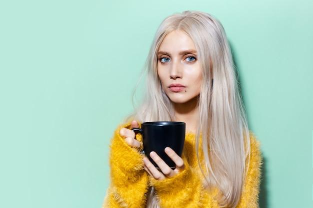 Portret van een jong mooi meisje met blauwe ogen, met zwarte kop op een achtergrond van pastelgroen van kleur. het dragen van gele trui.