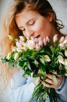 Portret van een jong mooi meisje met een boeket rozen dichtbij venster. krullend stromend rood haar.
