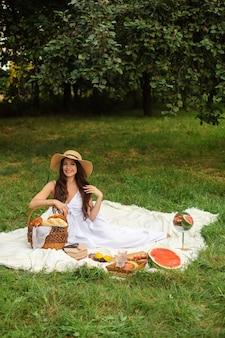 Portret van een jong mooi meisje met zelfs witte tanden, een mooie glimlach in een strohoed en een lange witte jurk hebben een picknick in de tuin