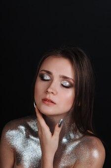 Portret van een jong mooi meisje met zilveren pailletten. kapsel van bruin haar, schone, gebruinde huid, mooie lichte make-up, roze lippenstift op de lippen. de schoonheid van het gezichtsmodel.
