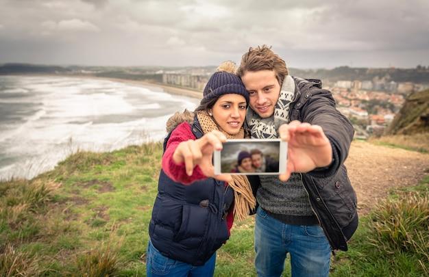 Portret van een jong mooi stel dat selfie-foto's maakt in een smartphone met zee en donkere bewolkte lucht op de achtergrond