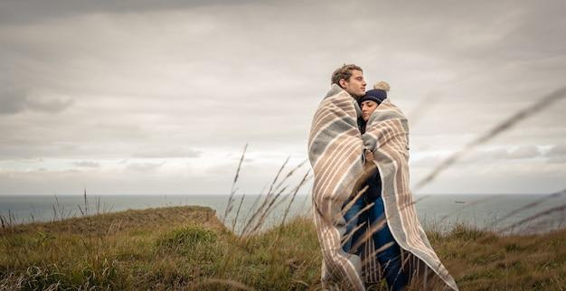 Portret van een jong mooi stel omarmen onder deken in een koude dag met zee en donkere bewolkte lucht op de achtergrond