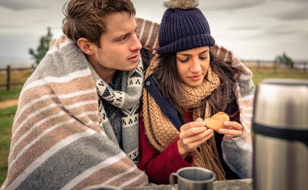 Portret van een jong mooi stel onder deken dat muffin eet op een koude dag met zee en donkere bewolkte lucht op de achtergrond