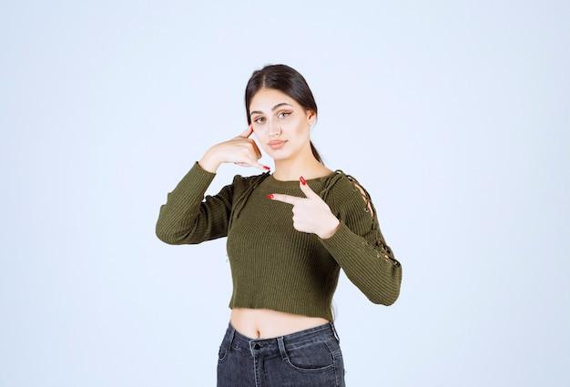 Portret van een jong mooi vrouwenmodel dat een telefoonroepteken doet en met een wijsvinger opzij wijst.