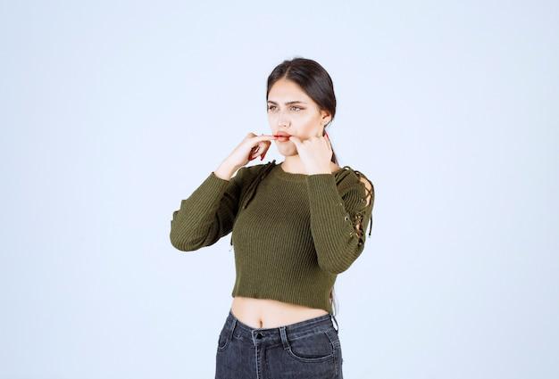 Portret van een jong mooi vrouwenmodel dat met haar vingers fluit.