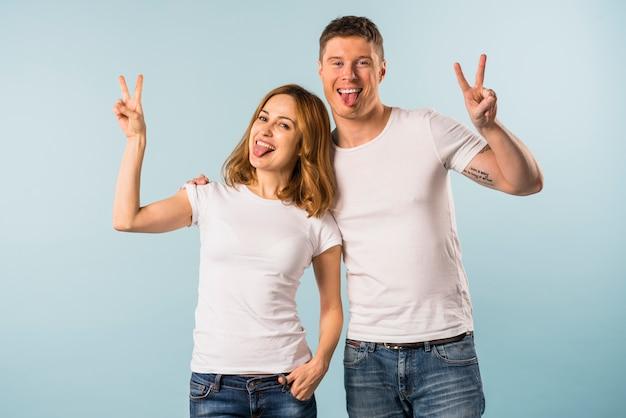 Portret van een jong paar dat uit haar tong steekt die vredesteken toont