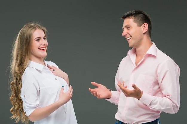 Portret van een jong paar dat zich tegen grijze achtergrond bevindt