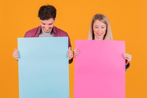Portret van een jong paar die blauw en roze aanplakbiljet bekijken tegen een oranje achtergrond