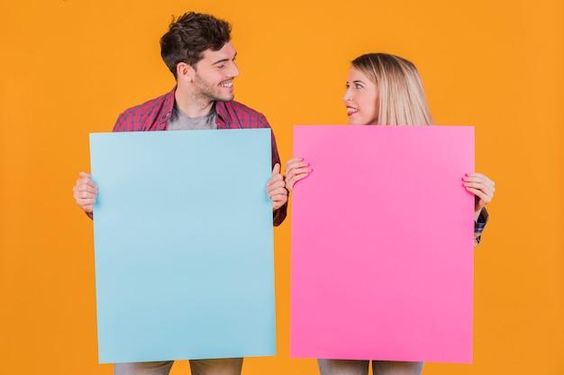Portret van een jong paar die blauw en roze aanplakbiljet houden tegen een oranje achtergrond