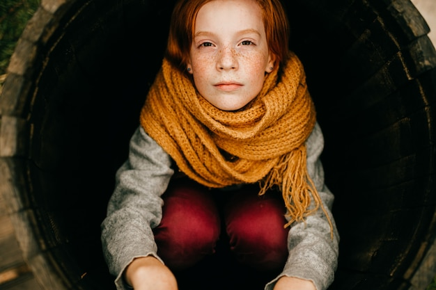 Portret van een jong roodharig meisje met sproeten close-up dragen oranje sjaal zitten in de ronde buis