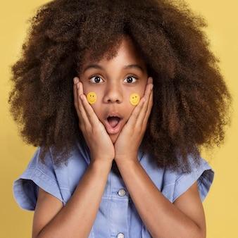 Portret van een jong schattig meisje poseren met emoji-stickers op haar gezicht