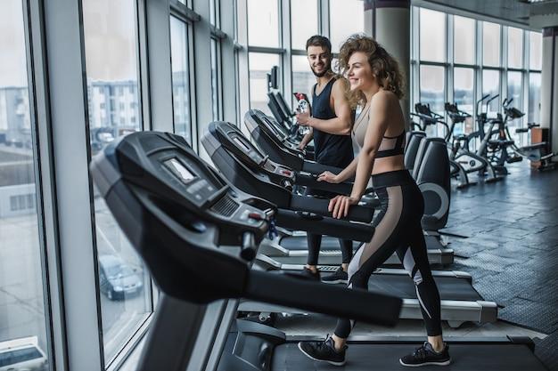 Portret van een jong sportpaar dat cardiotraining maakt in een moderne sportschool